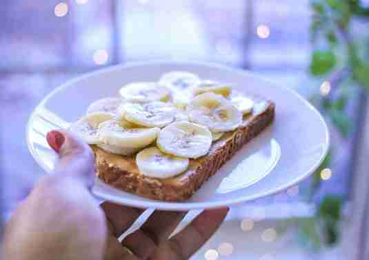 A person holding a plate of sliced bananas and peanut butter on toast