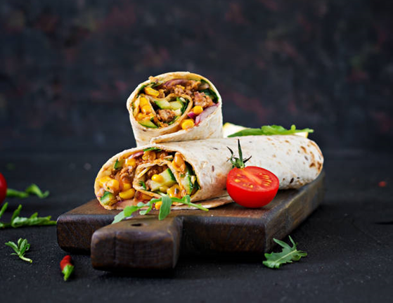 Two veggie burritos served on wooden board with arugula leaves scattered on table as well