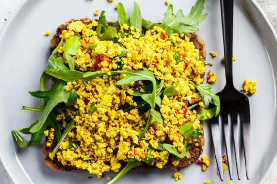 Vegan tofu scramble with arugula leaves on toast served on a dining plate next to a fork